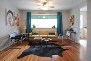 Ian's living room showing touches of Southwestern decorating, including cowhide rug & Native American powwow photographs